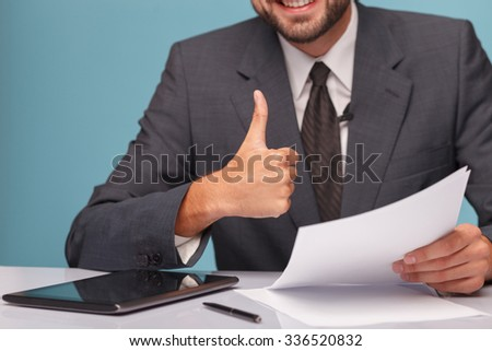 Close up of hands of young reporter giving thumb up. He is sitting at the table and smiling at studio. The man is holding documents. There is a tablet on the desk - stock photo