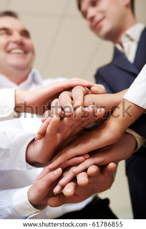 Close-up of hands on top of each other symbolizing support - stock photo