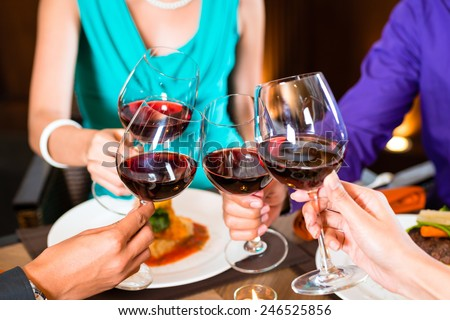 Close up of hands toasting in restaurant - stock photo