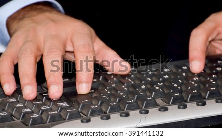 Close-up of hands touching buttons of black computer keyboard
