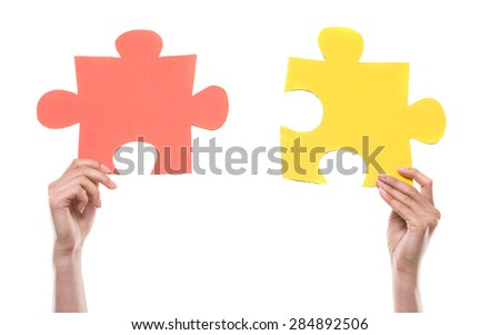 Close-up of hands trying to connect jigsaw puzzles over white background.