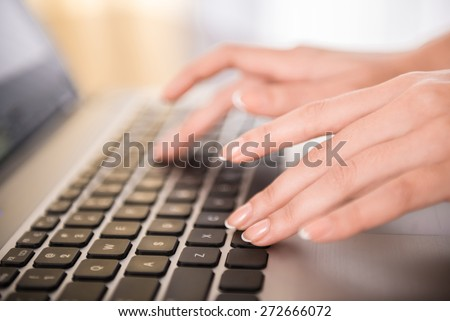 Close-up of hands typing on laptop keyboard in the office. - stock photo