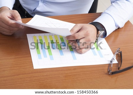 Close-up of hands with a pen and calculator on some document.