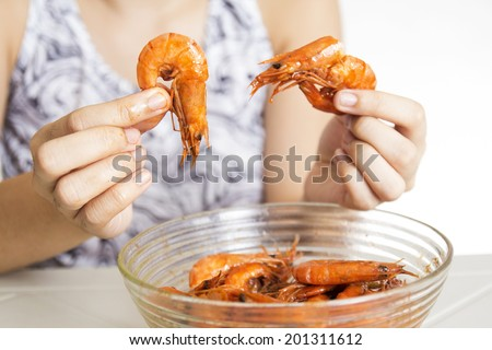 Close up of hands with cooked shrimp. - stock photo