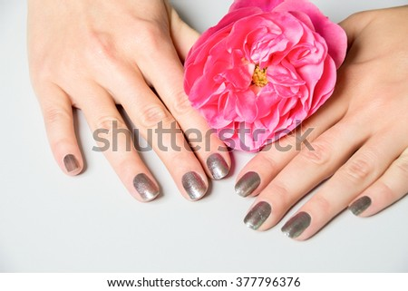 Close up of hands with metallic fingernail paint over spread out pink rose petals