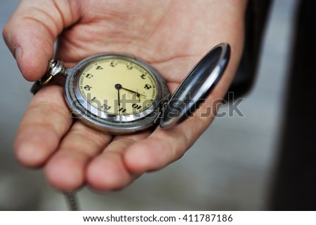 close up of hands with vintage pocket watch retro