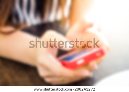 Close up of hands woman using cell phone under the golden sun. for blur - stock photo