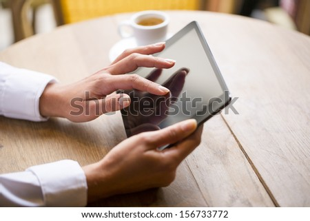 Close up of hands woman using her tablet pc in restaurant,cafe - stock photo