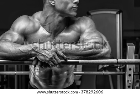 Close up of handsome bodybuilder guy prepare to do exercises with barbell in a gym. Black and white photo. - stock photo