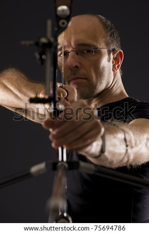 Close up of handsome bowman in black on black background aiming with bow and arrow, front view with focus on eyes.