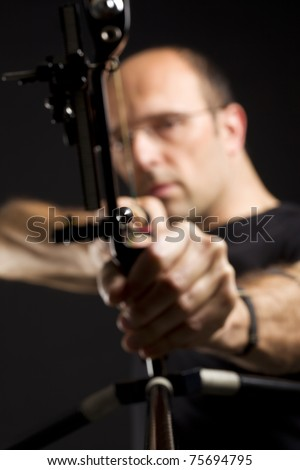 Close up of handsome bowman in black on black background aiming with bow and arrow, front view with focus on arrow tip. - stock photo