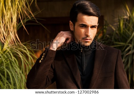close up of handsome young man with attitude, young male fashion model wearing semi formal jacket in outdoors - stock photo