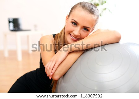 Close up of happy and beautiful woman with fitness ball at home - stock photo