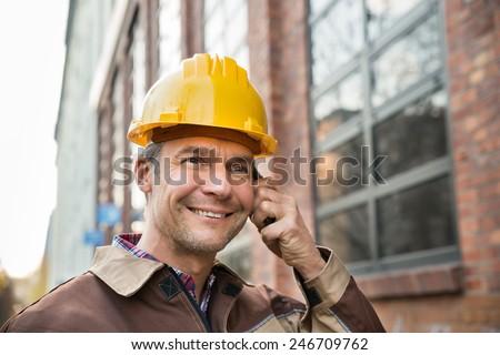 Close-up Of Happy Builder Wearing Hardhat Talking On Walkie Talkie - stock photo