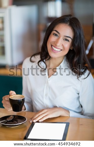 Close-up of happy businesswoman using digital tablet while having coffee in café - stock photo