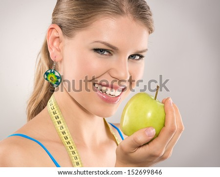 Close-up of happy diet woman loosing weight by eating healthy food. Young attractive Caucasian female model with green apple and scale. - stock photo