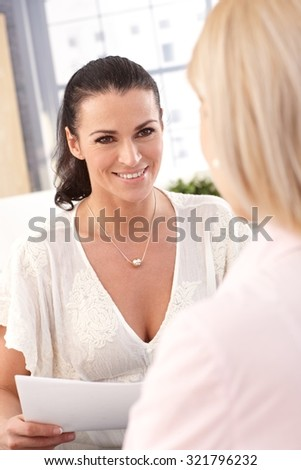 Close up of happy female casual brunette office worker with business papers, smiling. - stock photo