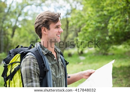 Close-up of happy man with map looking away - stock photo