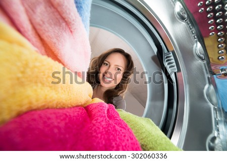 Close-up Of Happy Woman View From Inside The Washer With Clothes - stock photo