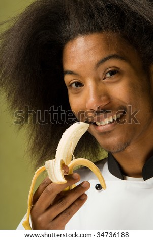 Close Up of Happy Young African American Chef Holding a Banana - stock photo
