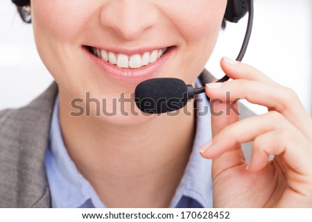 Close-up Of Happy Young Female Telephone Operator Talking On Headphones - stock photo
