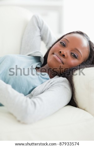 Close up of happy young woman taking a rest on the sofa