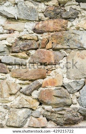 Close-up of hard wall made of raw natural stones. Can be used as texture or background