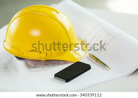 Close up of hardhat, blueprints, pen and cellphone