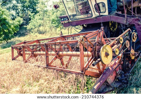Close-up of harvesting combine in grain and wheat crops. Agricultural activities at rural countryside - stock photo