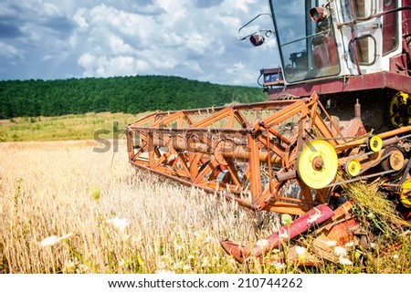 close-up of harvesting combine in wheat crops, agricultural industry at countryside  - stock photo