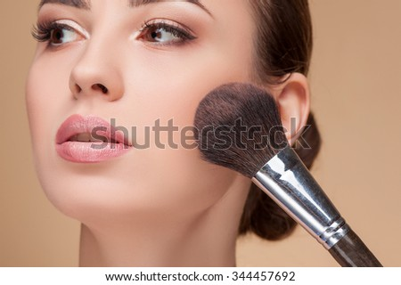 Close up of head of cheerful girl attending beauty shop. The visagiste is applying powder on female check with a brush. The lady is looking forward with serenity - stock photo