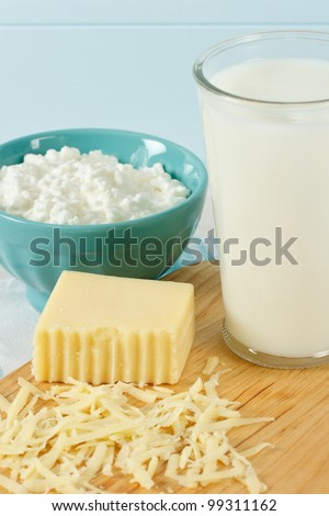 Close up of healthy dairy products includes milk, cottage cheese and shredded Swiss cheese
