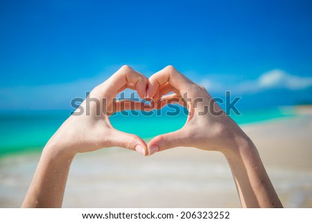 Close up of heart made by female hands background the turquoise ocean - stock photo