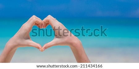 Close up of heart made by hands background turquoise ocean