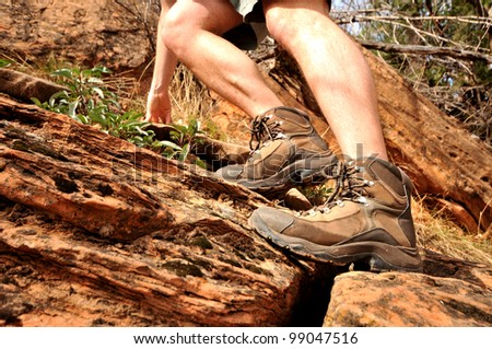 Close up of hiking boots and legs climbing up rocky trail