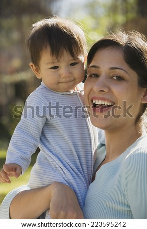 Close up of Hispanic mother holding baby outdoors - stock photo