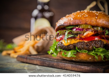 Close-up of home made tasty burgers on wooden table. - stock photo