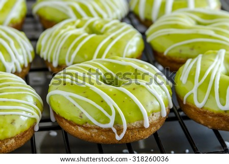 Close up of homemade baked caramel apple donuts with green apple glaze sitting on wire baking rack after apple cider drizzle was applied - stock photo