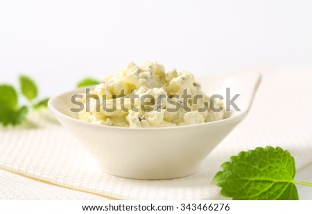 close up of homemade cheese spread with herbs in white bowl