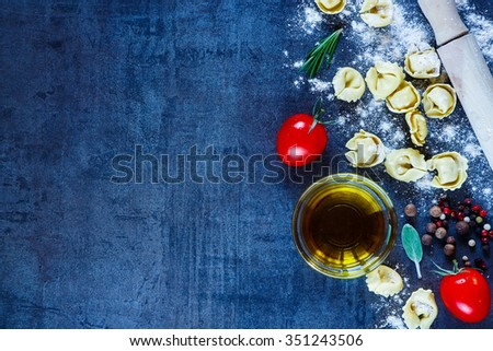 Close up of homemade Italian pasta tortellini, tomatoes, flour, fresh herbs, spices and olive oil on dark vintage background with space for text. Healthy eating or cooking concept. - stock photo