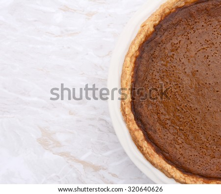 Close-up of homemade pumpkin pie with copy space on kitchen worktop - stock photo