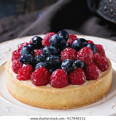 Close up of Homemade tart with custard, fresh raspberries and blueberries, served on white vintage plate with iron teapot on textile napkin over old wooden table. Dark rustic style. Square image - stock photo