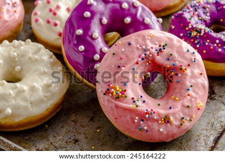 Close up of homemade vanilla bean donut with pink icing sitting on metal baking pan - stock photo