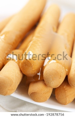 Close-up of honey breadsticks in plate.