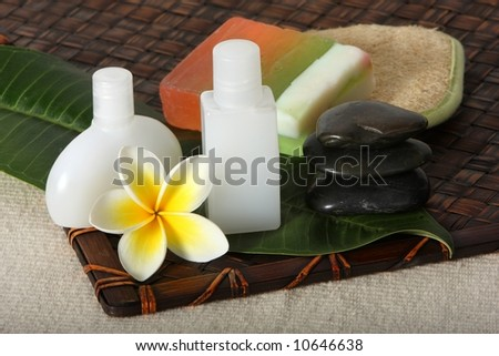 close up of hot massage river stones with yellow and white frangiapani flower and leaf with beauty day spa products - soap, lotions and loofah - stock photo