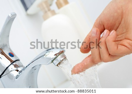 Close-up of human finger trying how hot the water is - stock photo