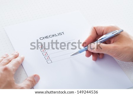 Close-up Of Human Hand Filling Check Boxes On Form - stock photo