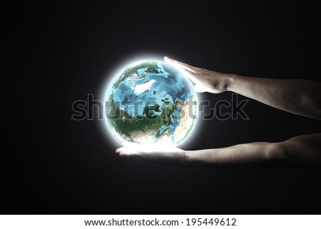 Close up of human hand holding Earth planet. Elements of this image are furnished by NASA
