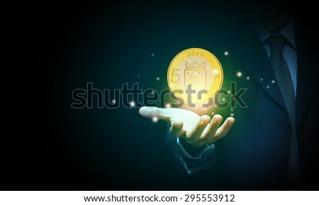 Close up of human hand holding golden euro coin
