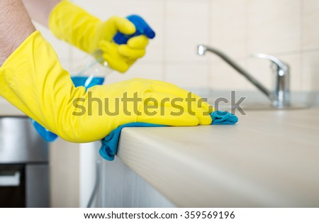 Close up of human hand in protective gloves holding mop and spray bottle and wiping kitchen countertop - stock photo